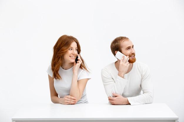 Coppia di redhead uomo, donna parla al telefono
