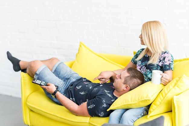 Coppia di relax sul divano e guardare la televisione a casa