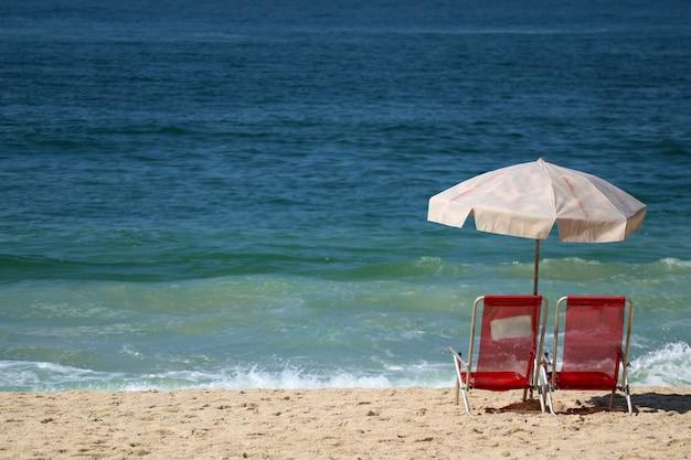 Coppia di sedie a sdraio rosse e ombrellone rosa pallido sulla spiaggia di sabbia contro le onde dell'oceano