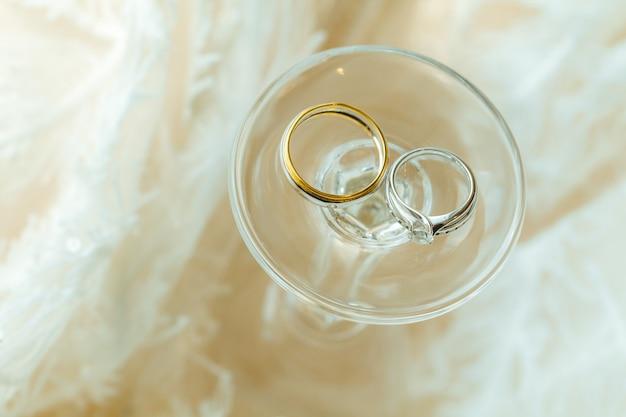 Coppia di sposi anelli di diamanti posizionati con bicchiere di vino e tessuto.
