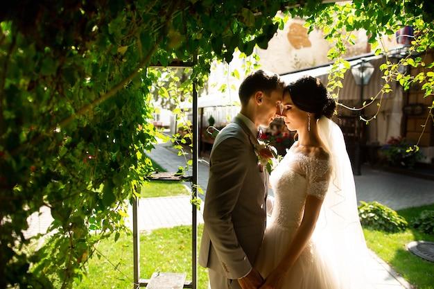 Coppia di sposi di lusso, sposa e sposo, in posa nel romantico cortile della città vecchia