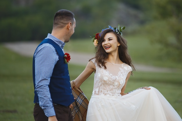 Coppia di sposi novelli sposi a un matrimonio nella foresta verde della natura stanno baciando il ritratto della foto.