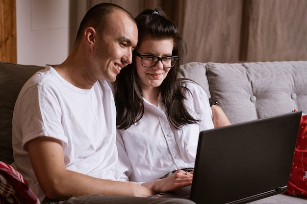 Coppia di sposi seduti a casa sul divano con il computer portatile ordinare merci online
