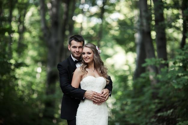 Coppia di sposi sorridenti che propongono all'aperto