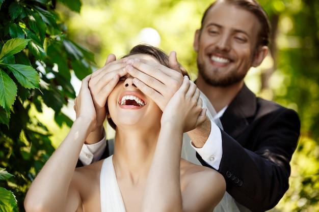 Coppia di sposi sorridenti. sposo che copre gli occhi della sposa con le mani.