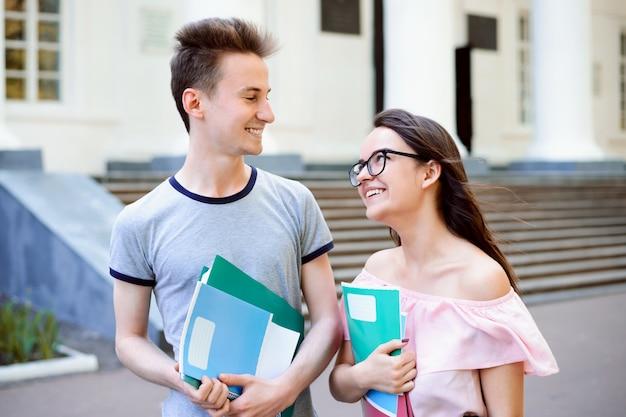 Coppia di studenti felici che camminano e parlano vicino al vecchio campus dopo le lezioni