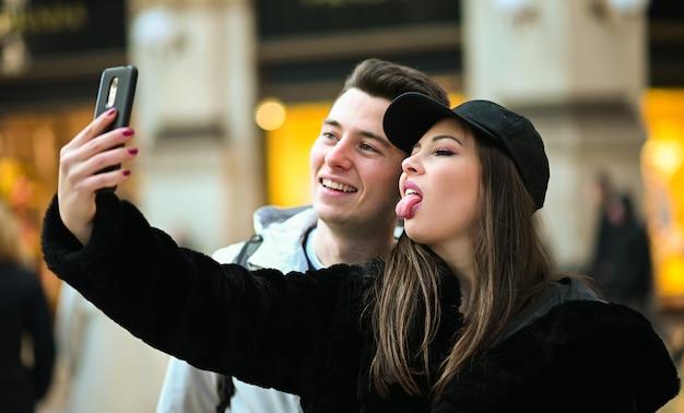 Coppia di turisti che fanno selfie divertenti a milano