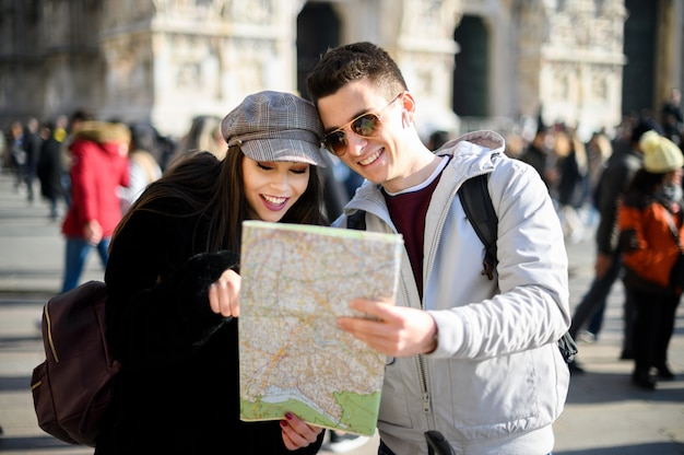 Coppia di turisti in città guardando una mappa e discutendo della prossima destinazione