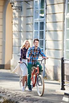 Coppia di turisti in sella a una bicicletta tandem lungo la strada della città