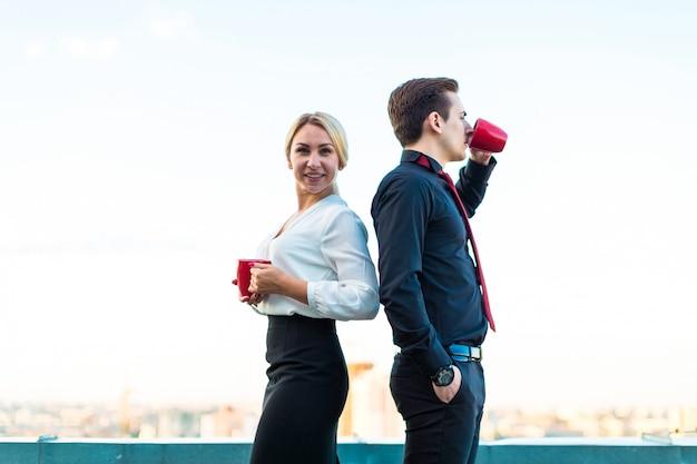 Coppia di uomini d'affari, attraente uomo bruna e bella donna bionda in piedi sul tetto e bere caffè