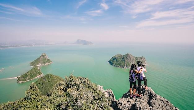 Coppia di viaggiatori in piedi e scattare foto in cima alla montagna e godendo per la bellezza