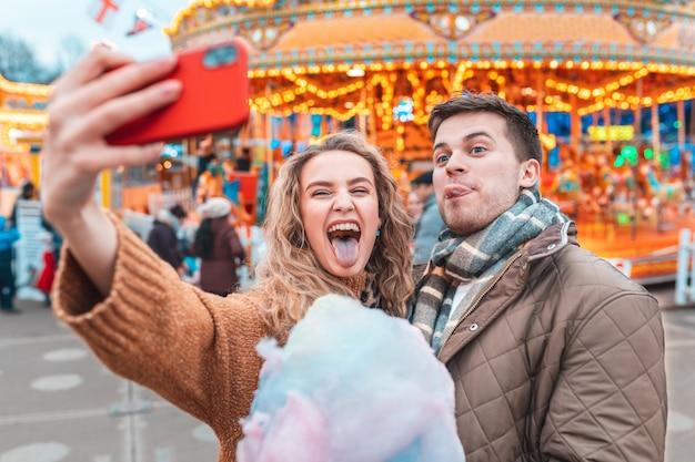 Coppia divertendosi e prendendo un selfie al parco di divertimenti a londra