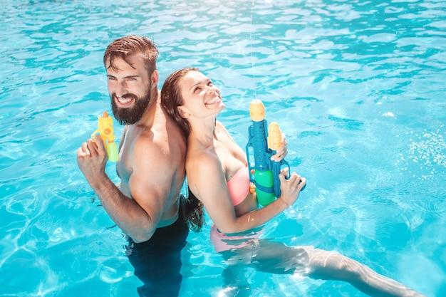 Coppia divertente si trova in piscina. pongono e sorridono. la ragazza alza lo sguardo. tengono in mano pistole ad acqua. sono pronti a sparare.