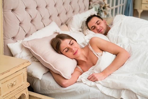 Coppia dorme nel letto con piumone