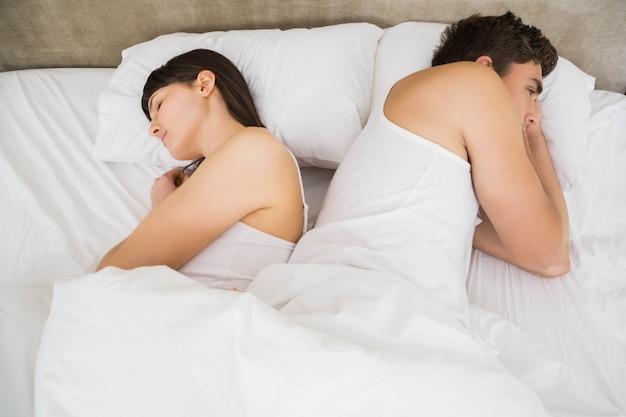 Coppia dormire schiena contro schiena sul letto dopo una discussione