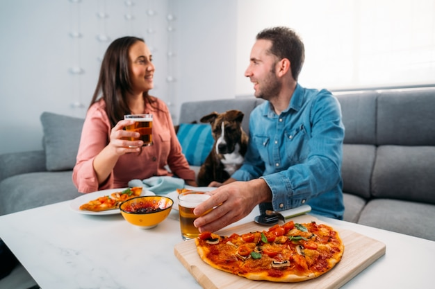 Coppia e il loro cane seduto sul divano e mangiare la pizza italiana fatta in casa nel loro salotto