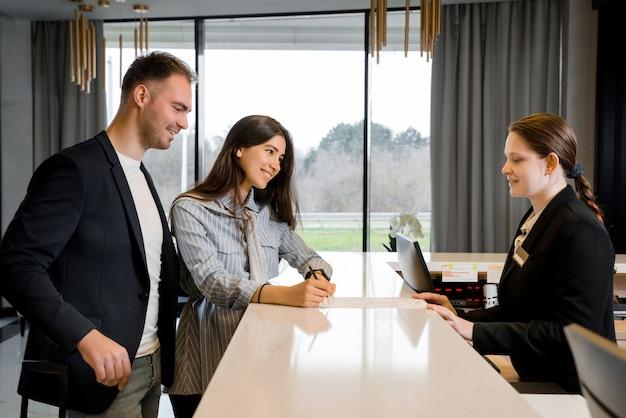 Coppia e receptionist al banco in hotel. giovane coppia in viaggio d'affari facendo il check-in in hotel