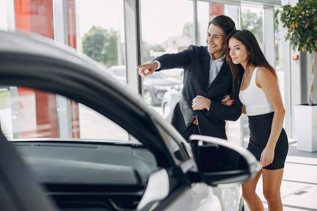 Coppia elegante e alla moda in un salone di auto