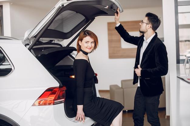 Coppia elegante ed elegante in un salone di auto