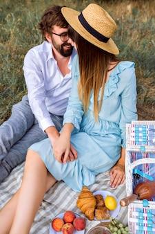 Coppia elegante facendo gustoso picnic all'aperto
