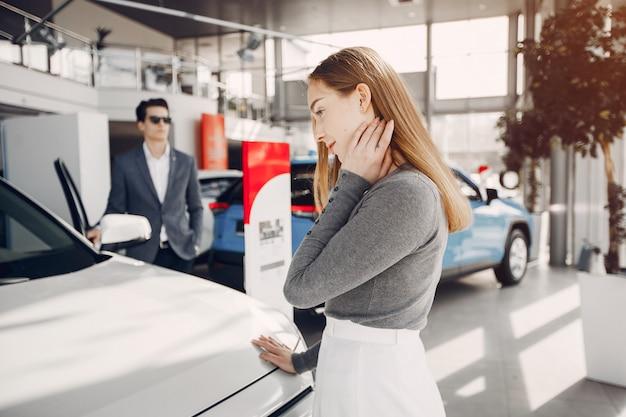 Coppia elegante in un salone di auto