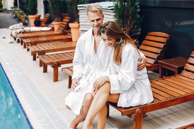 Coppia elegante seduto vicino a una piscina