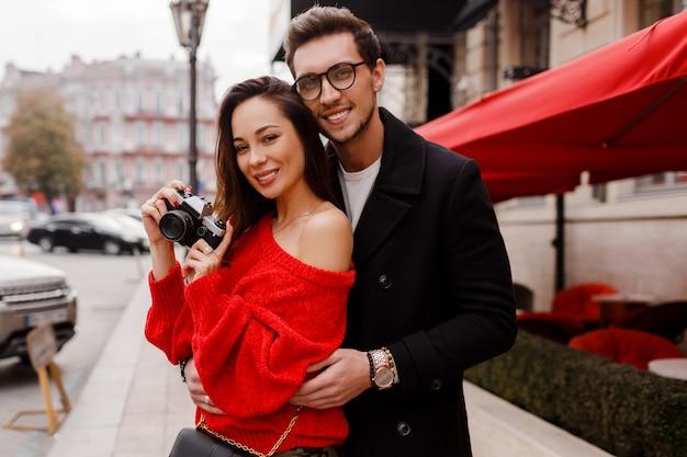 Coppia europea imbarazzante e in posa per strada in vacanza. atmosfera romantica. bella donna castana tenendo la fotocamera a pellicola.