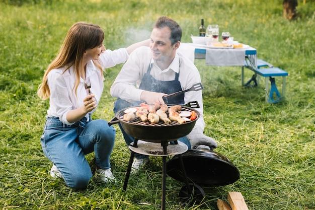 Coppia facendo un barbecue in natura