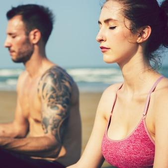 Coppia facendo yoga in spiaggia