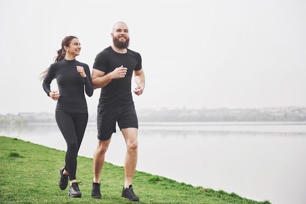 Coppia fare jogging e correre all'aperto nel parco vicino all'acqua. giovane uomo e donna barbuti che si esercitano insieme nella mattina