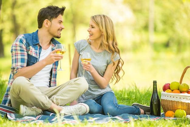 Coppia fare picnic nel parco e bere vino.