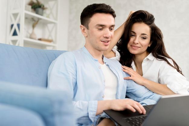 Coppia felice a casa con il portatile