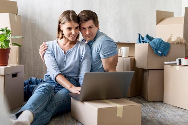 Coppia felice a casa con scatole e laptop pronti a partire