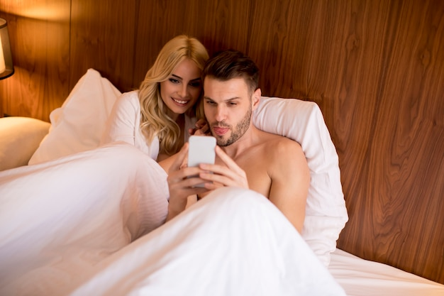 Coppia felice a letto a casa e utilizzare il telefono cellulare