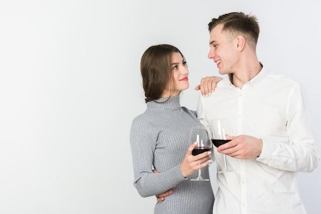 Coppia felice clanging bicchieri di vino
