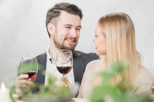 Coppia felice con bicchieri di vino rosso