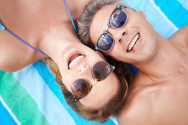 Coppia felice con gli occhiali da sole sulla spiaggia