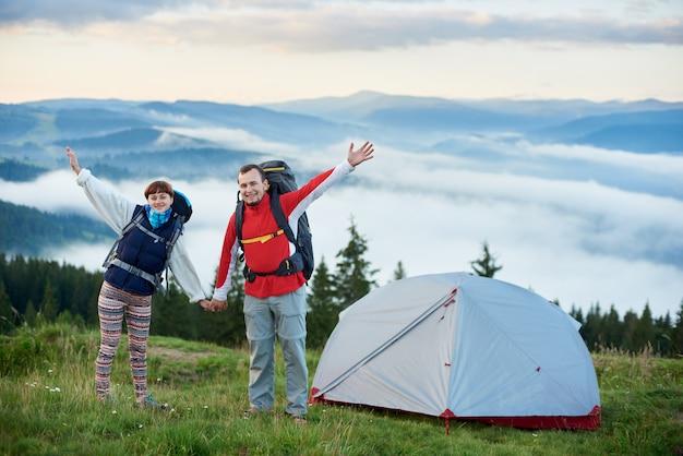 Coppia felice con zaini vicino alla tenda tenendosi per mano sullo sfondo dello splendido scenario delle possenti montagne dei carpazi su cui giace una foschia e il cielo è bellissime nuvole.