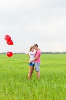 Coppia felice di un uomo e di una donna innamorata vestita in stile country che tiene palloncino rosso.