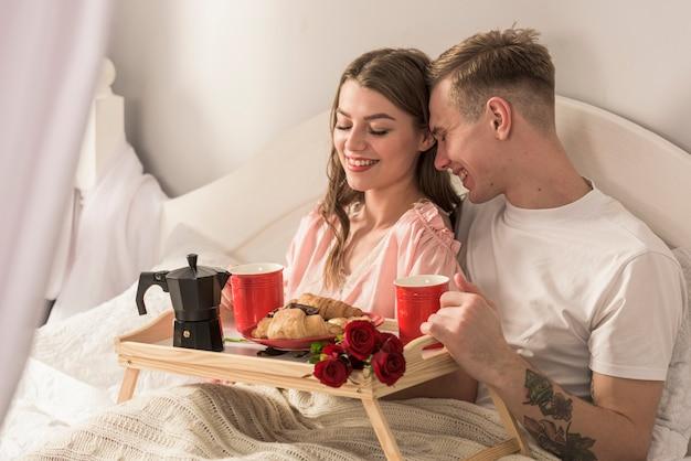 Coppia felice facendo colazione a letto