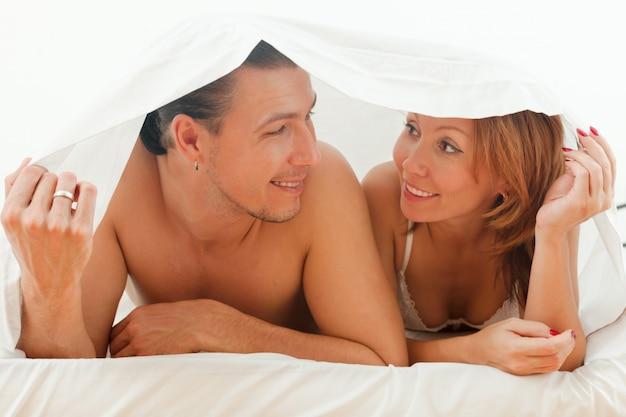 Coppia felice giocando a letto