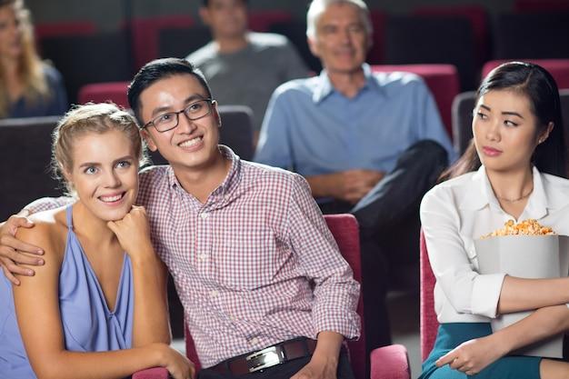 Coppia felice guardare film, ragazza in cerca di loro