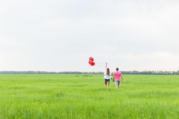 Coppia felice in amore tenendo palloncino rosso, vista posteriore