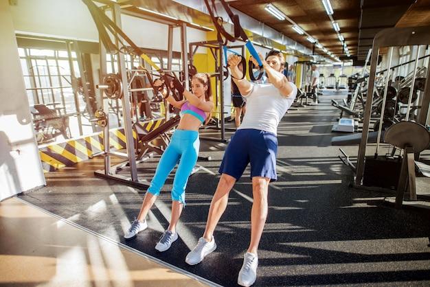 Coppia felice in forma nell'allenamento in palestra. usare trx per i loro esercizi.