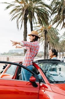 Coppia felice in piedi in auto
