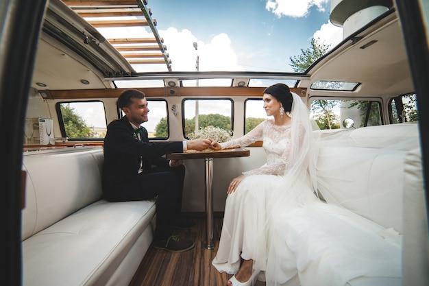 Coppia felice in posa in auto dopo il matrimonio