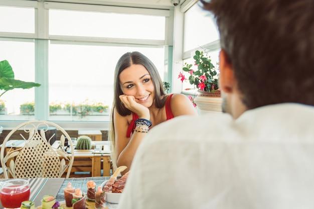 Coppia felice incontri in un ristorante. donna innamorata che ha una conversazione con il suo ragazzo