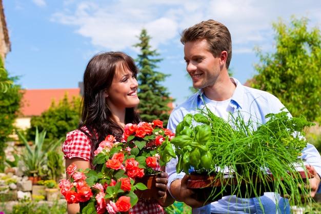 Coppia felice orgogliosa delle loro erbe e fiori in vaso