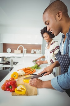 Coppia felice preparazione verdure in cucina