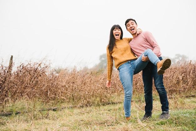 Coppia felice ridendo e scherzando in campagna